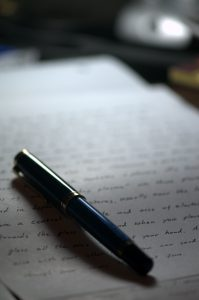 Artistic photo of a pen on a hand-written letter.
