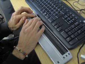 Close up of someone's hands as they read a braille display, with a keyboard nearby.